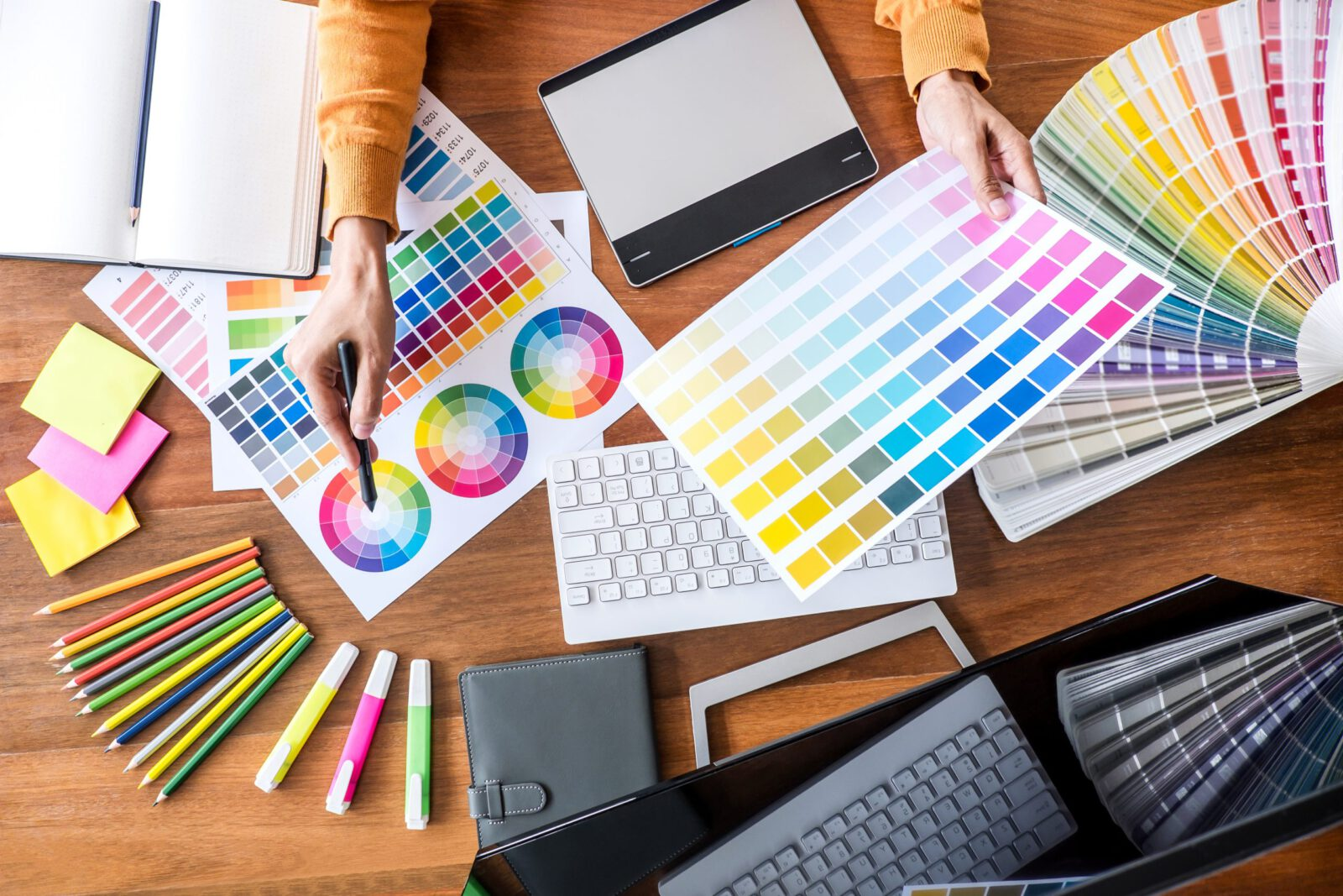 Image of female creative graphic designer working on color selection and drawing on graphics tablet at workplace with work tools and accessories, top view workspace.