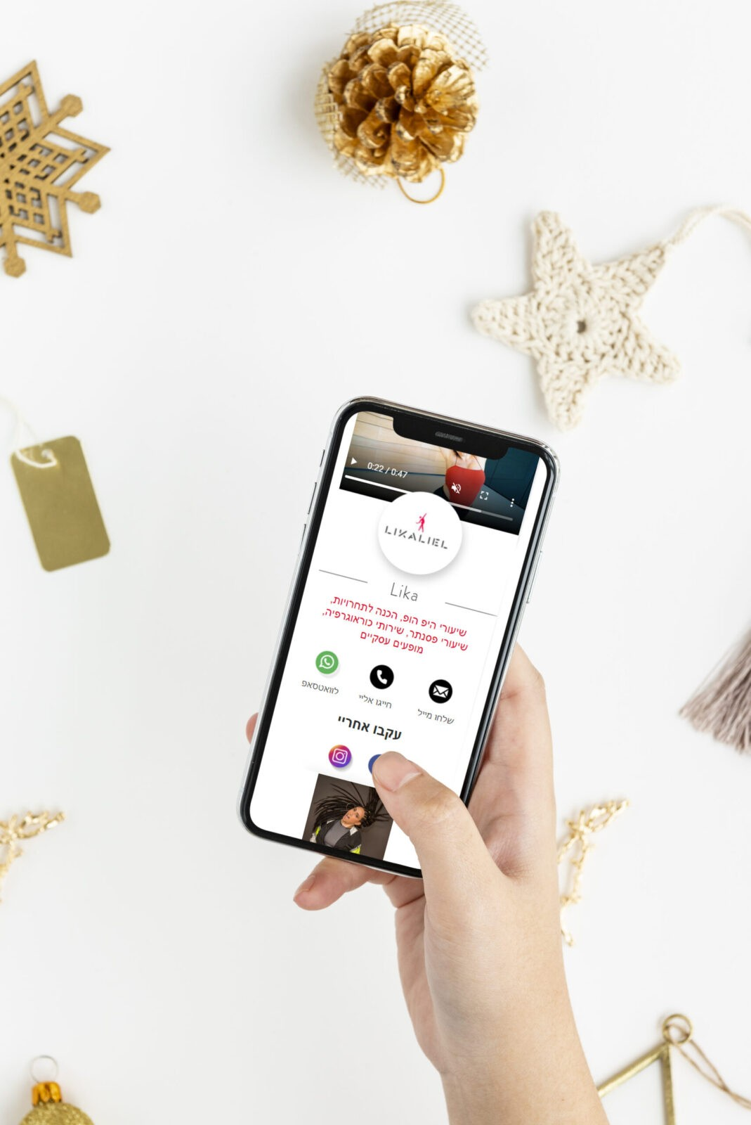 Woman holding her phone above gold Christmas ornaments mockup